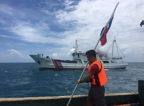 Một nhà hoạt động Philippines cầm quốc kỳ khi tàu hải cảnh Trung Quốc áp sát ở bãi cạn Scarborough, cách đảo chính Luzon của Philippines 230 km, tháng 6/2016. Ảnh:AFP.