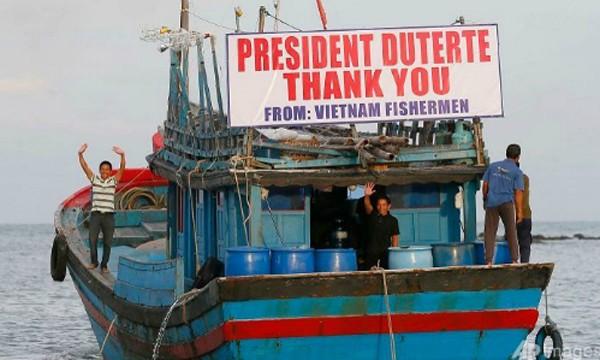 Ngư dân Việt vẫy tay chào tạm biệt Tổng thống Rodrigo Duterte và quan chức Philippines. Ảnh: AFP