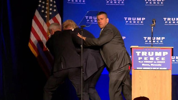 Ông Trump được các nhân viên an ninh đưa về phía sau sân khấu khi đang phát biểu. Ảnh: Reuters