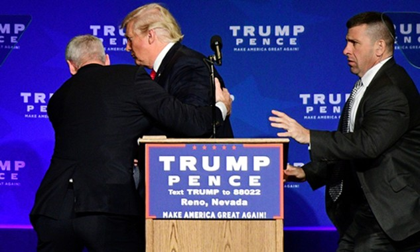 Ứng viên tổng thống đảng Cộng hòa Donald Trump được nhân viên an ninh hộ tống rời sân khấu trong sự kiện vận động ở bang Nevada ngày 5/11 khi nghi có mối đe dọa từ đám đông phía dưới. Ảnh: Reuters.