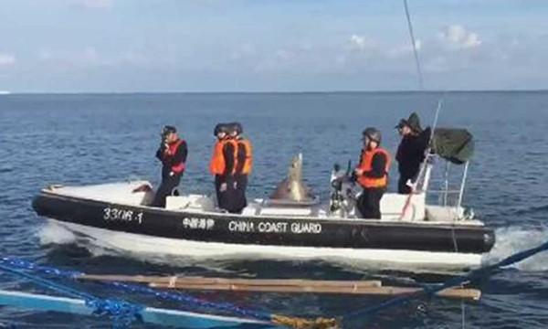Tuần duyên Trung Quốc đi trên xuồng cao tốc, chĩa súng xua đuổi ngư dân Philippines ở bãi cạn Scarborough hồi năm ngoái. Ảnh:ABS-CBN.