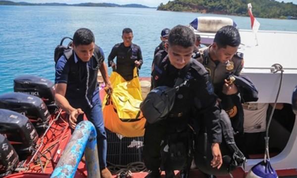Cảnh sát Indonesia mang túi đựng xác và mảnh vụn máy bay lên bờ. Ảnh:AFP