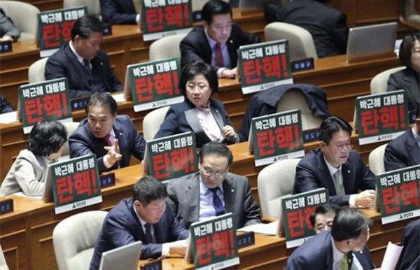 """Các nghị sĩ đối lập trongquốc hội Hàn Quốc giương bảng có dòng chữ """"Luận tội Tổng thống Park Geun-hye. Ảnh:AP"""