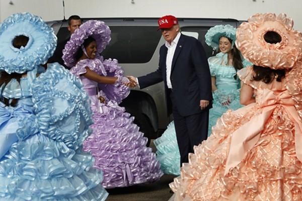 Các cô gái mặc váy chân phồng sặc sỡ chào đón ông Trump ở sân bay Mobile, Alabama hôm qua. Ảnh:Reuters
