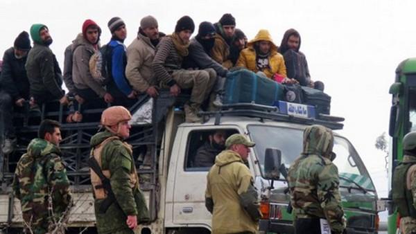 Lính chính phủ Syria và Nga giám sát đoàn xe chở các tay súng nổi dậy. Ảnh:BBC.