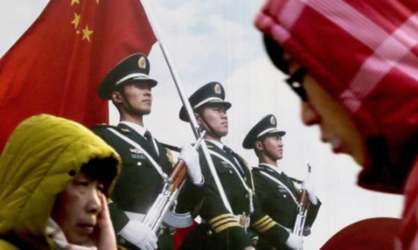 Người dân đi qua áp - phíchcủa quân đội Trung Quốc. Ảnh: AP