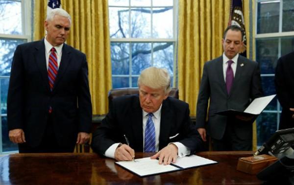 Ông Trump ký sắc lệnh hành pháp (executive order) dưới sự chứng kiến của Phó tổng thống - Mike Pence (trái) và Chánh Văn phòng Nhà Trắng -Reince Priebustại Phòng Bầu dụcngày 23/1 (theo giờ Washington). Ảnh:Reuters