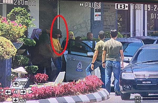 Nghi phạm thứ hai (mặc áo vàng) bị cảnh sát bắt giữ. Ảnh:CCTV News