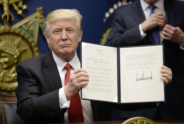 Tổng thống Donald Trump ký một sắc lệnh hành pháp tại trụ sở Bộ Quốc phòng Mỹ hôm 27/1 (Ảnh: Politifact)