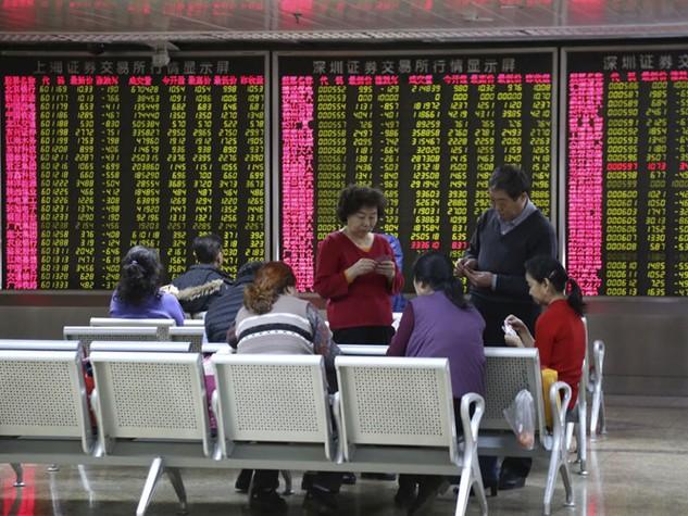 Các nhà đầu tư Trung Quốc chơi bài trước một bảng điện tử thể hiện các chỉ số chứng khoán ở Bắc Kinh - Ảnh: Reuters
