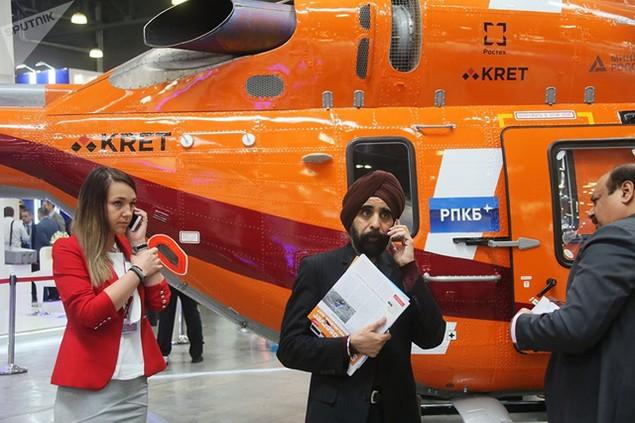 Các du khách đứng trước một trực thăng hạng nhẹ Ansat của Nga