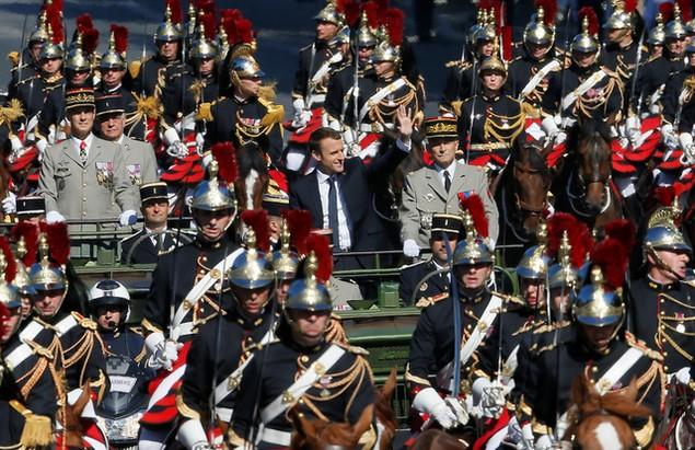 Tổng thống Pháp Emmanuel Macron vẫy tay chào công chúng khi đứng cạnh Tổng tham mưu trưởng các lực lượng vũ trang Pháp Pierre de Villiers trên chiếc xe jeep quân sự. (Ảnh: Reuters)